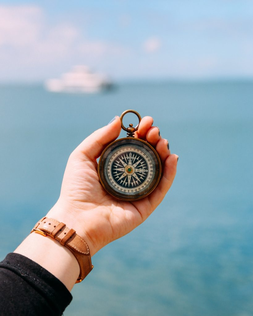 Person holding compass with the sea in the background