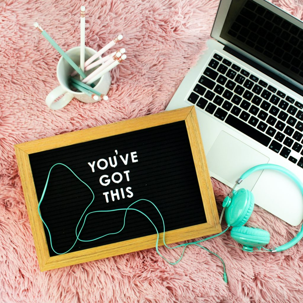 Tutors International one-to-one online private tuition: 'you've got this' text written on a tablet next to a laptop, pens, and headphones